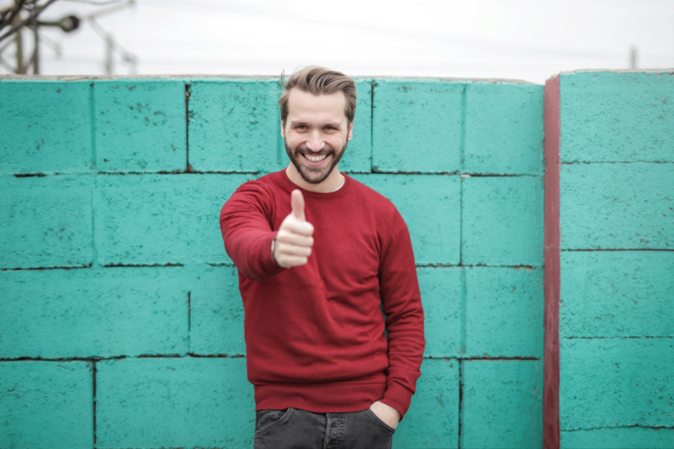 man thumbs up happy smile red jumper jersey blue brick wall.jeans fashio male people